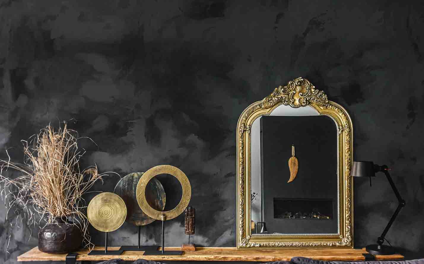 Gold and natural decoration with a mirror in front of a black wall painted in Marrakech Walls Slate