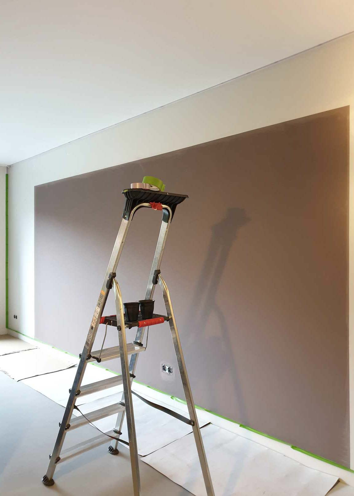 Before picture of the wall painted in a light brown with a white border and a ladder in front
