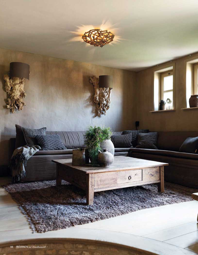 Living room with tan coloured walls, wooden light furnishings, and a dark grey couch