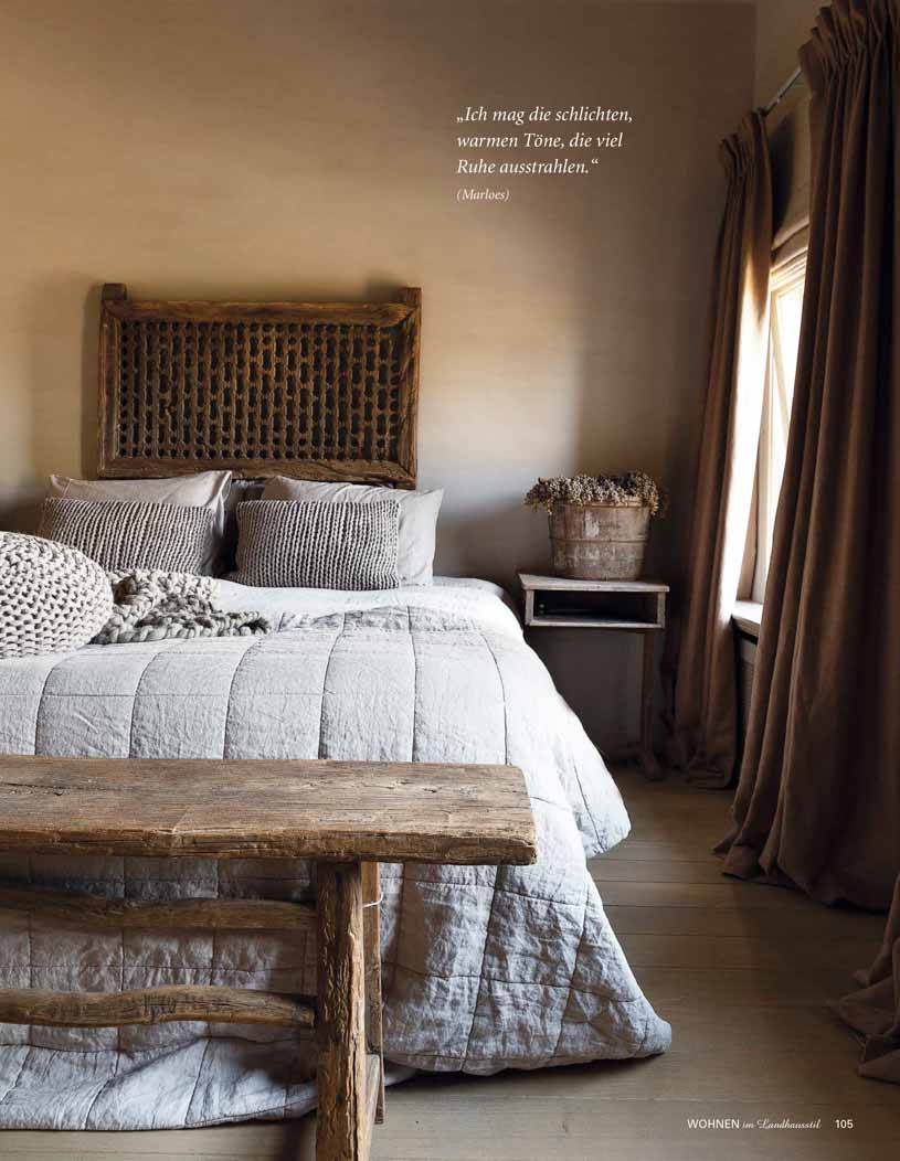 Rustic bedroom with wooden furniture, tan coloured walls, and grey bed linnen
