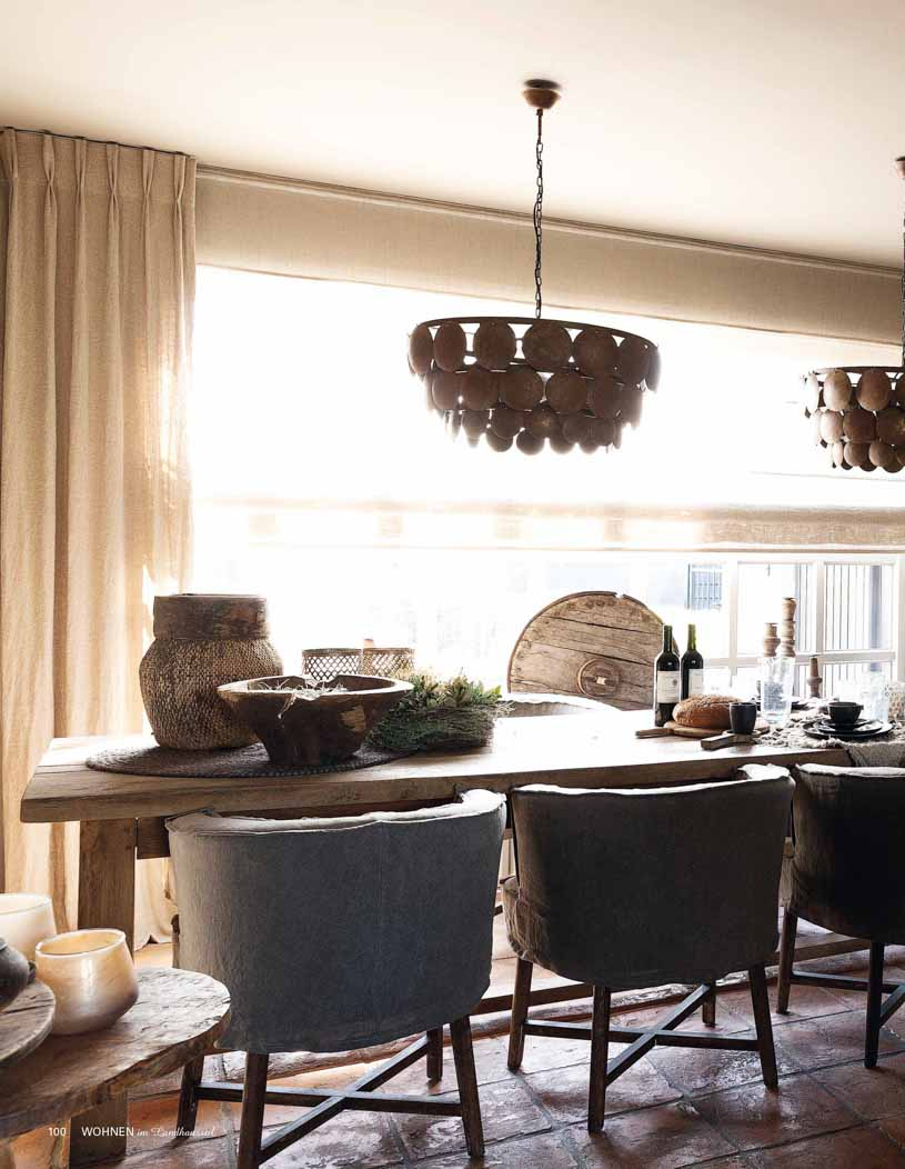 Dining area with long wooden table, rustic chandeliers, beige curtains and large grey chairs